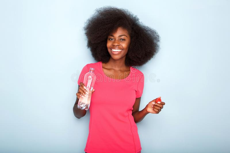 Close up happy young black woman holding bottle of water royalty free stock image