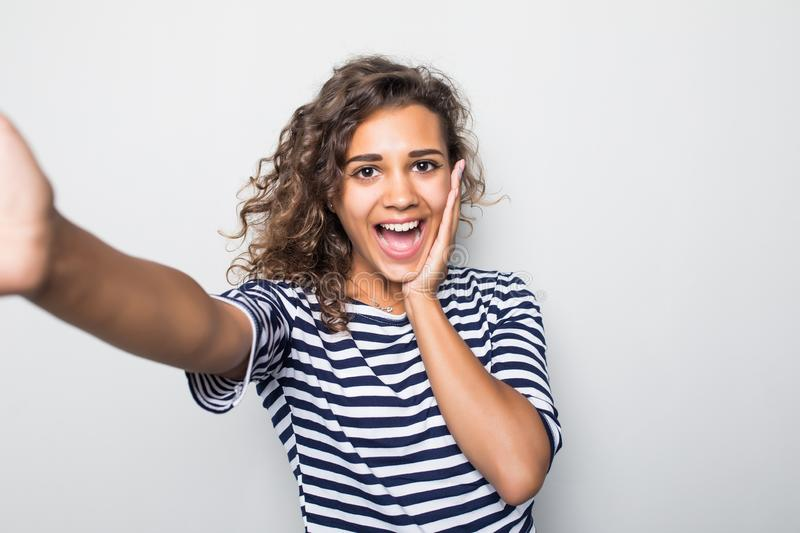 Close up portrait of a happy young curly mulatto woman making selfie against isolated white background royalty free stock photos