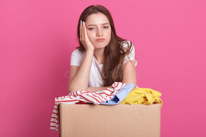 Close up portrait of happy young woman with clothes donation standing over rose background, packing reusable clothes for poor royalty free stock photo