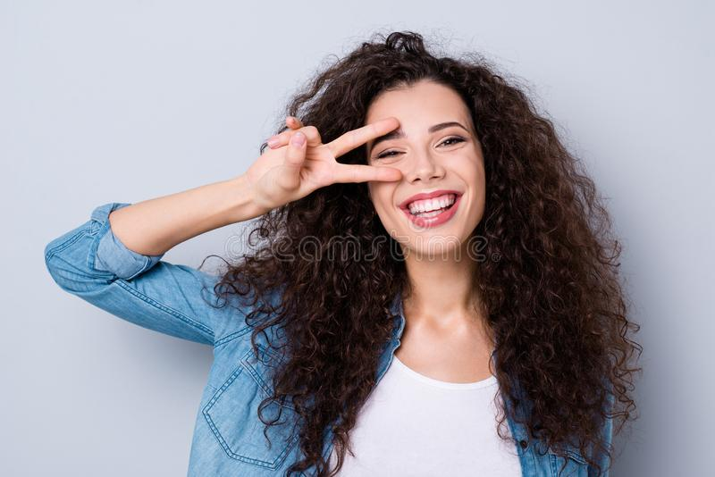 Close-up portrait of her she nice cute charming attractive lovely lovable cheerful optimistic funny toothy wavy-haired. Girl showing v-sign near eye over gray stock photos