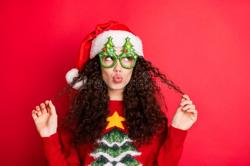 Close-up portrait of her she nice-looking attractive lovely pretty cheerful flirty wavy-haired Santa girl pouted lips. Playing with curls isolated, over bright royalty free stock image