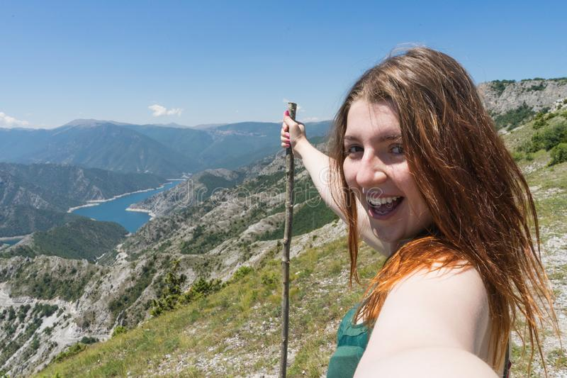Close up portrait Hiker girl smiling and laughing holding a wood stick. Excursionist red head woman taking a selfie with smart stock photos