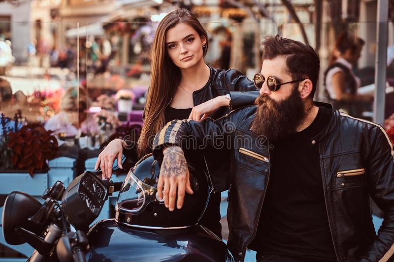 Close-up portrait of a hipster couple - bearded brutal male in sunglasses dressed in a black leather jacket and his royalty free stock photo