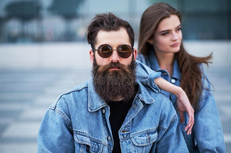 Close-up portrait of a hipster couple of a brutal bearded male in sunglasses and his girlfriend dressed in jeans jackets stock photo