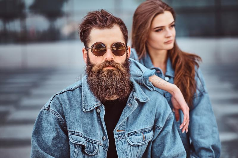 Close-up portrait of a hipster couple of a brutal bearded male in sunglasses and his girlfriend dressed in jeans jackets royalty free stock photo