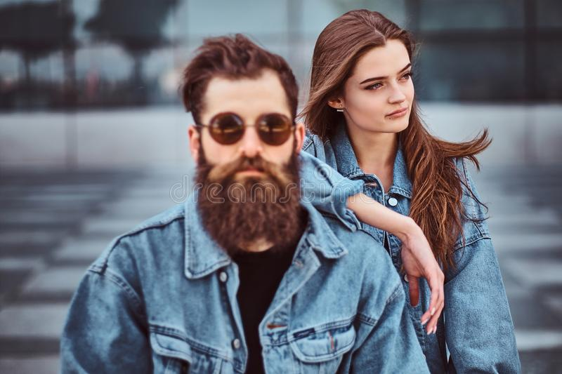 Close-up portrait of a hipster couple of a brutal bearded male in sunglasses and his girlfriend dressed in jeans jackets royalty free stock photos