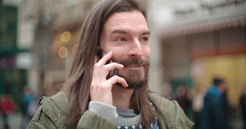 Close up portrait of hipster man making phone call outdoors in a city. stock photo