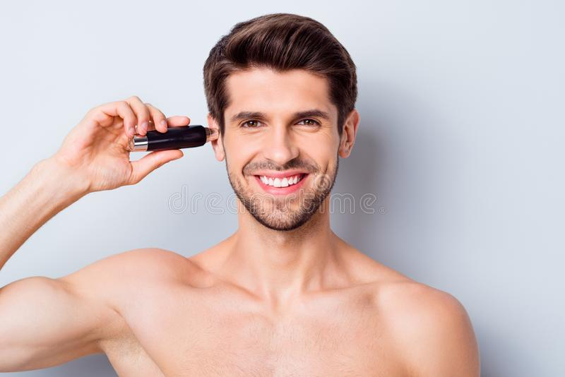 Close-up portrait of his he nice attractive bearded cheery brown-haired guy shaving picking cutting unwanted hair in ear stock photo