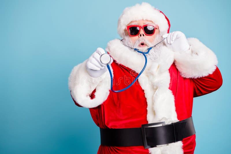 Close-up portrait of his he nice funky bearded Santa wearing mechanical retro phonendoscope making diagnosis listening. Close-up portrait of his he nice funky stock image
