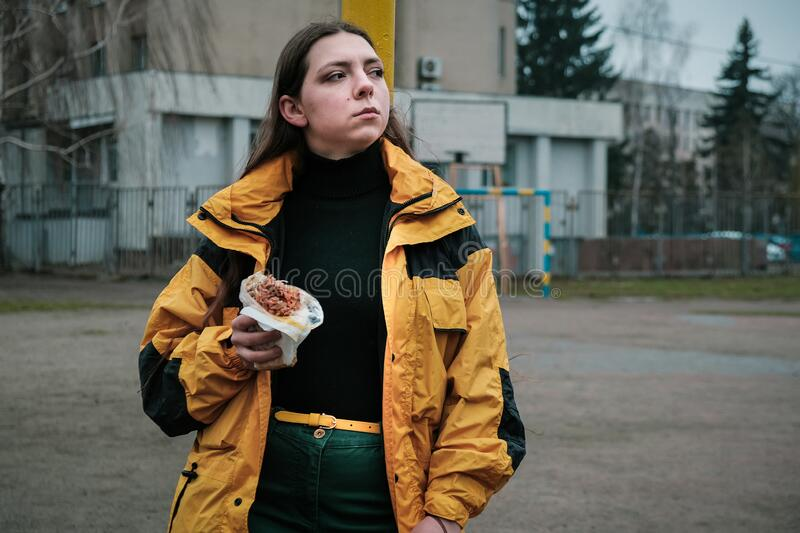 Hungry girl is eating fast street junk food stock photography
