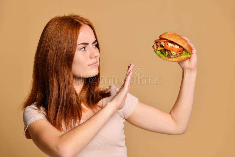 Close up portrait of a hungry young woman eating burger over nude background. Funny crazy smiling Skinny redhead girl in shorts holds a burger hamburger and royalty free stock images