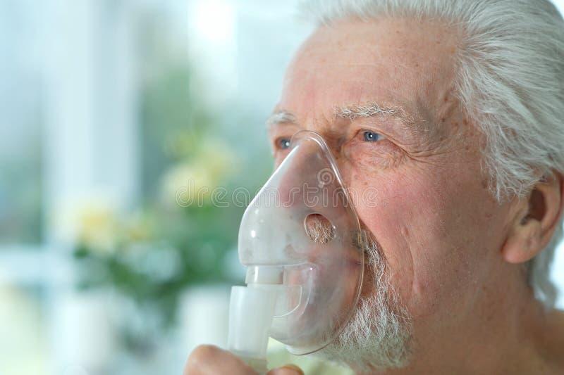 Close up portrait of ill senior man portrait with inhaler stock photo