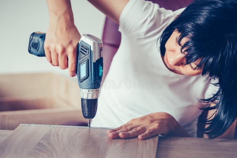 Close up portrait of  independent woman with a cordless drill assembling new furniture stock photos