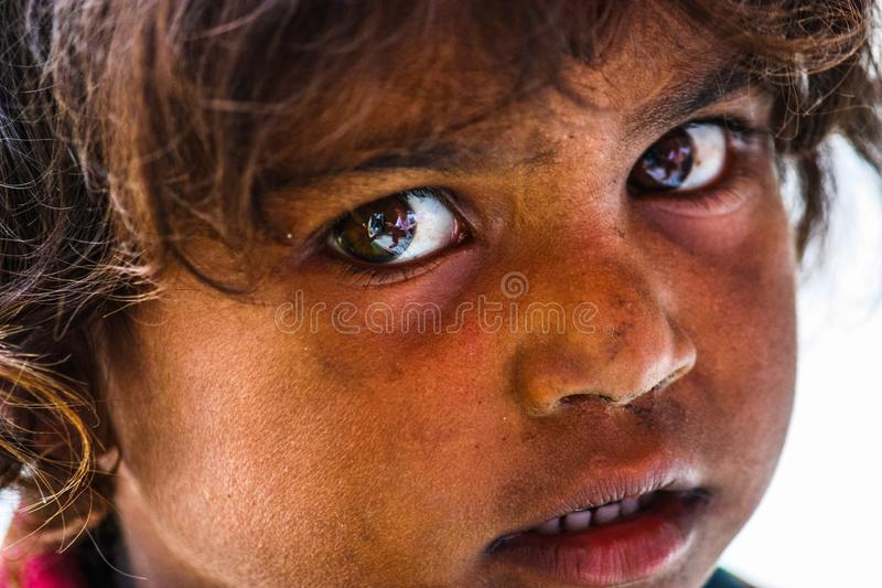 Udaipur, India - August 20, 2009: close up portrait of an Indian girl with an intense look asking for alms with her sister in stock photo