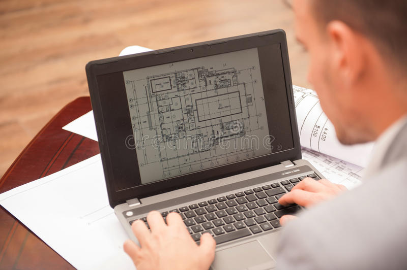 Close-up portrait of laptop with blueprints royalty free stock image