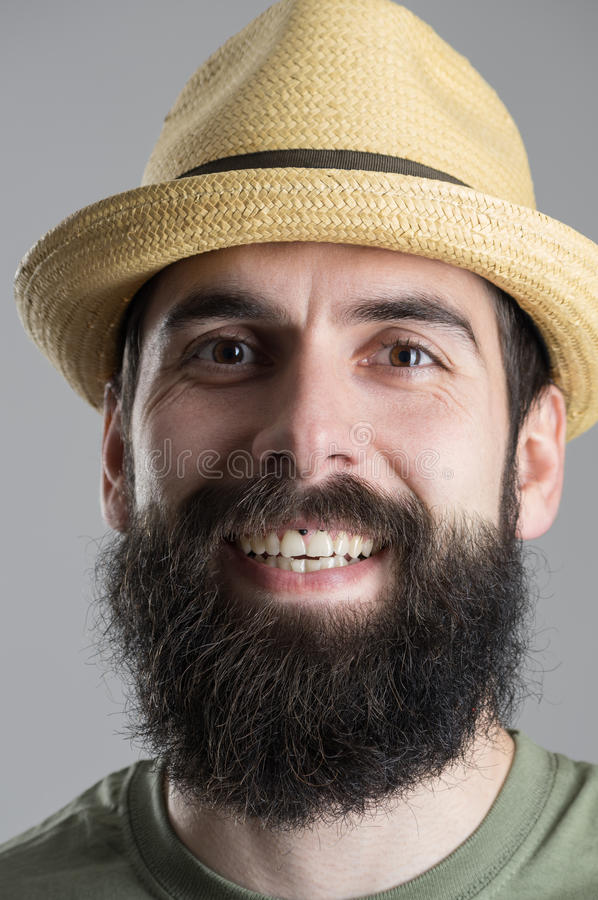 Close up portrait of laughing bearded man in straw hat looking at camera. stock image