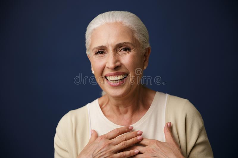 Close-up portrait of laughing mature woman, holding hands on her stock image