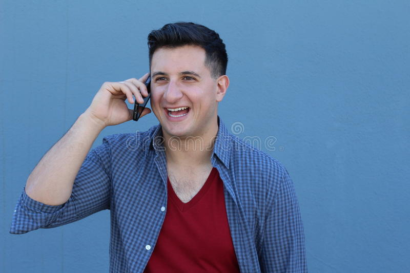 Close up portrait of laughing young man in talking by mobile phone over blue background.  royalty free stock images
