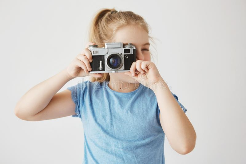 Close up portrait of little adorable girl with blonde hair in blue t-shirt going to take a picture of friends in school royalty free stock images