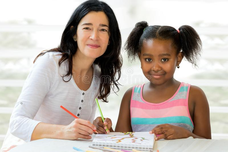 Little african girl and teacher drawing together. royalty free stock image