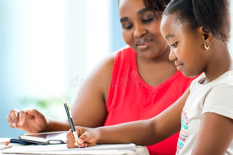 Little african girl doing home work with supervisor. Close up portrait of little african girl doing home work. Teacher giving private after school lessons with stock images