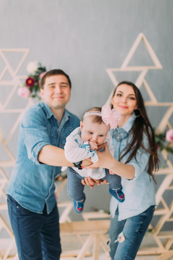 The close-up portrait of the little baby with the bow on the head being swung by her parents. stock photos