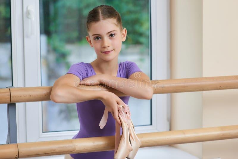 Close up portrait of little ballerina. Beautiful young ballet dancer posing near ballet barre. Adorable little ballerina stock photos