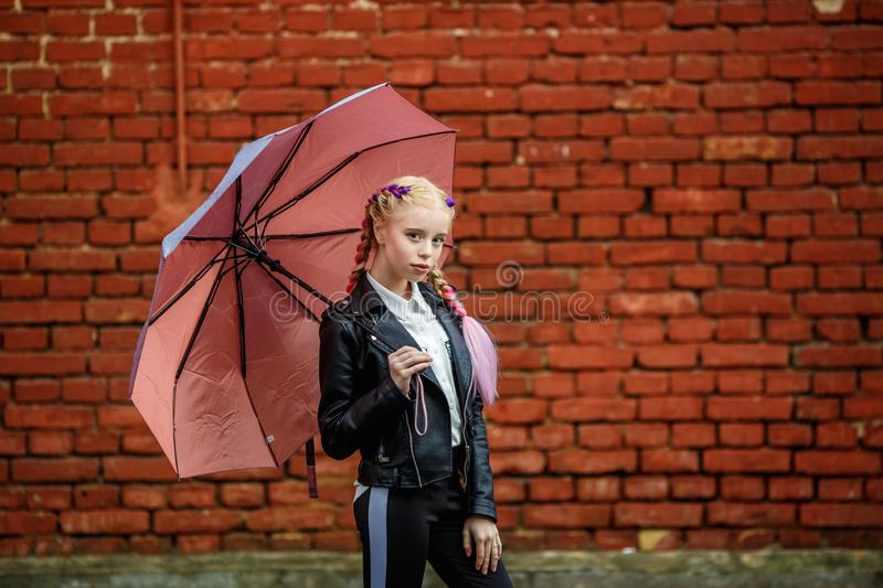 Close up portrait of little beautiful stylish kid girl with an umbrella in the rain near red brick wall as background stock images