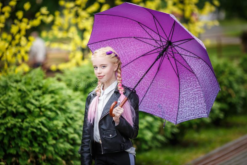Close up portrait of little beautiful stylish kid girl with an umbrella in the rain on park.  stock photos