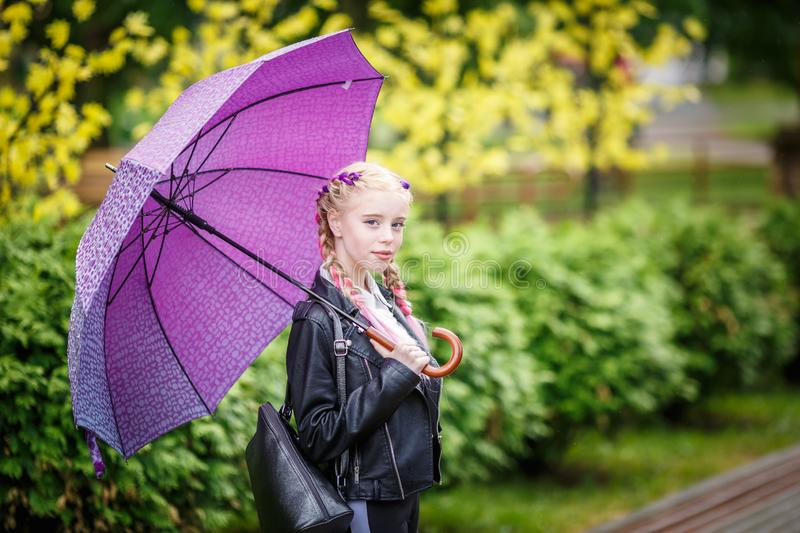 Close up portrait of little beautiful stylish kid girl with an umbrella in the rain on park.  stock photo