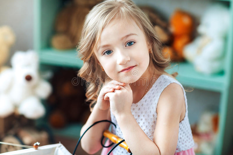 Close-up portrait of a little blond girl smiling in a children`s room royalty free stock image