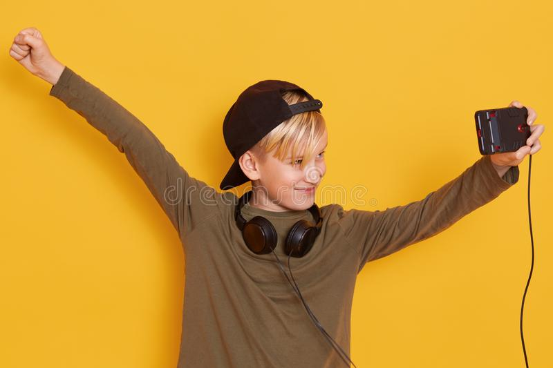 Close up portrait of little boy holding his modern cellphone and watching video,using wireless Internet and headphones, child stock photos
