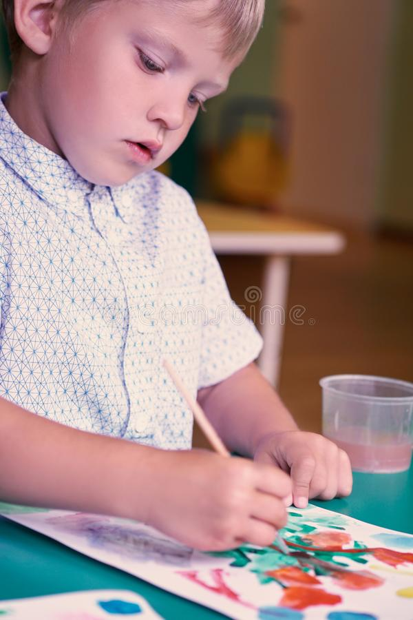 Close up portrait of little caucasian blond boy drowing with watercolor paints. Activities with children in kindergarten royalty free stock photography