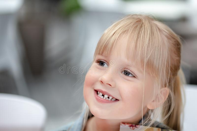 Close-up portrait of little cute blond caucasian girl in casual jeans clothes smiling outdoors. Adorable innocent happy royalty free stock images
