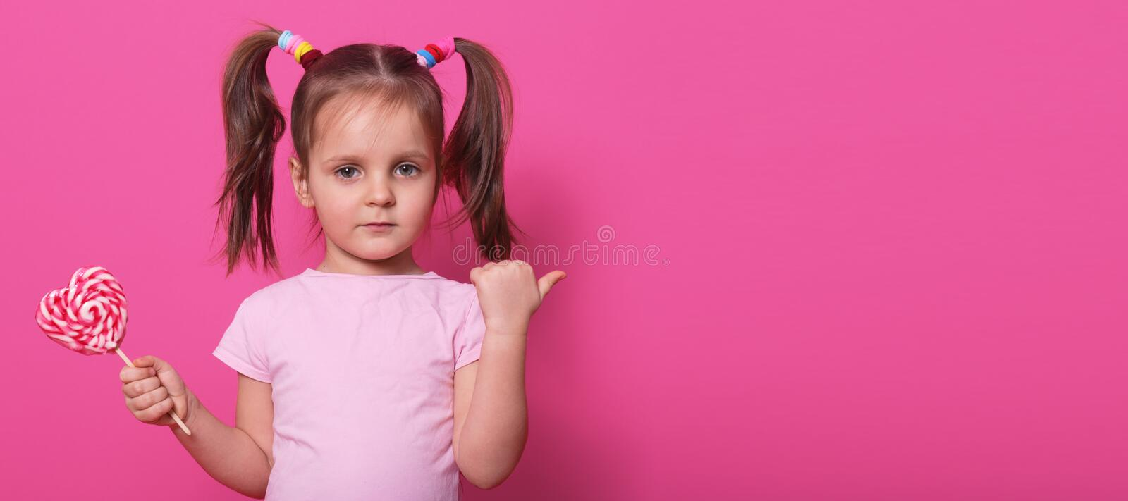 Close up portrait of little cute child, looking directly at camera, holding heart bright lollipop, pointing aside with her thumb, stock images