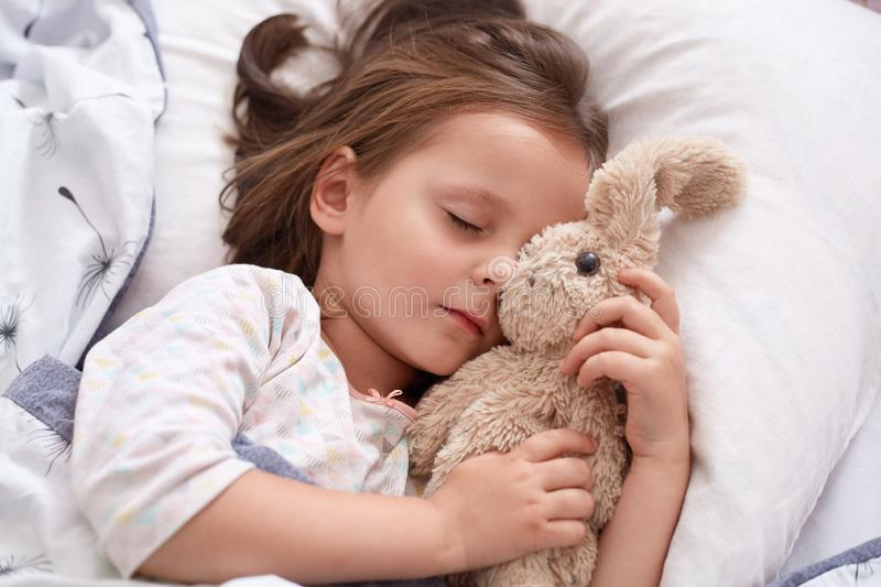 Close up portrait of little girl hugging her teddy bear and being happy, having rest after interesting day in kinder garten. stock images