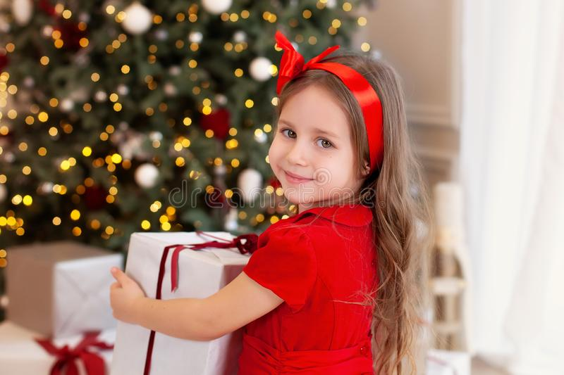Close-up portrait Little girl in a red dress laughs and enjoys the gift. Little girl opening a magical christmas present at home. stock photos