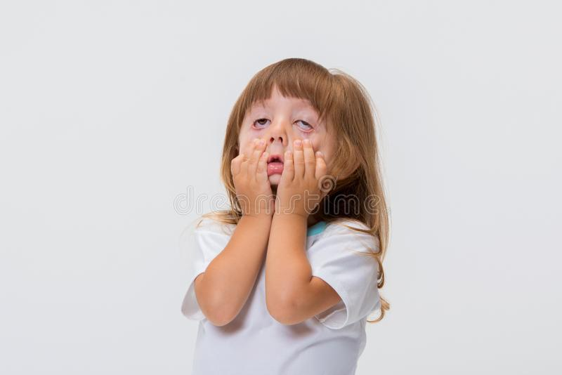 Close-up portrait of little girl`s face. Girl grimacing, covering her face with her hands. Close-up portrait of little girl`s face isolated on white background stock image