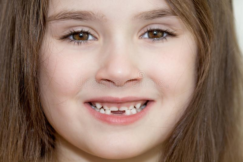 The close up portrait of little girl`s face with missing front lower milk teeth in a smiling mouth royalty free stock photo
