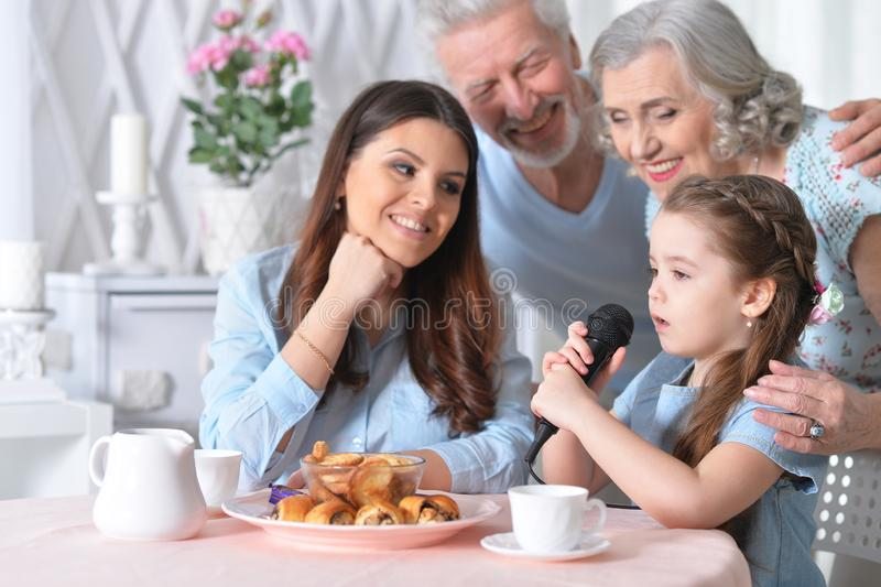 Close up portrait of little girl singing karaoke with mother and grandparents royalty free stock photography