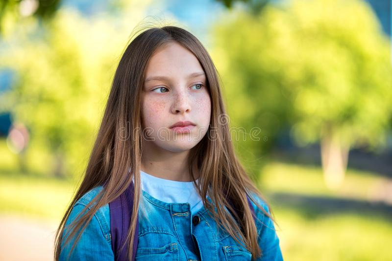 Close-up portrait. Little girl teenager. Summer in nature. Long hair freckles face. Emotion looks thoughtfully towards. Close-up portrait. Little girl teenager stock image