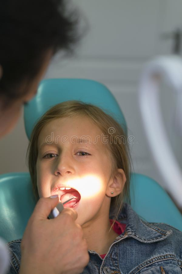 Close up portrait of a little smiling girl at dentist office. Dentist examining little girl's teeth in clinic. people, medicine, stock photography
