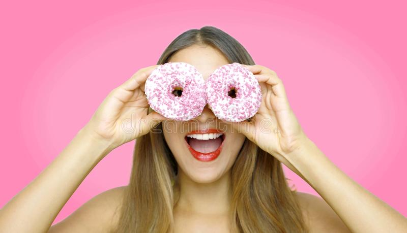 Close-up portrait of long-haired smiling girl having fun with sweets isolated on pink background. Attractive young woman with long stock photos