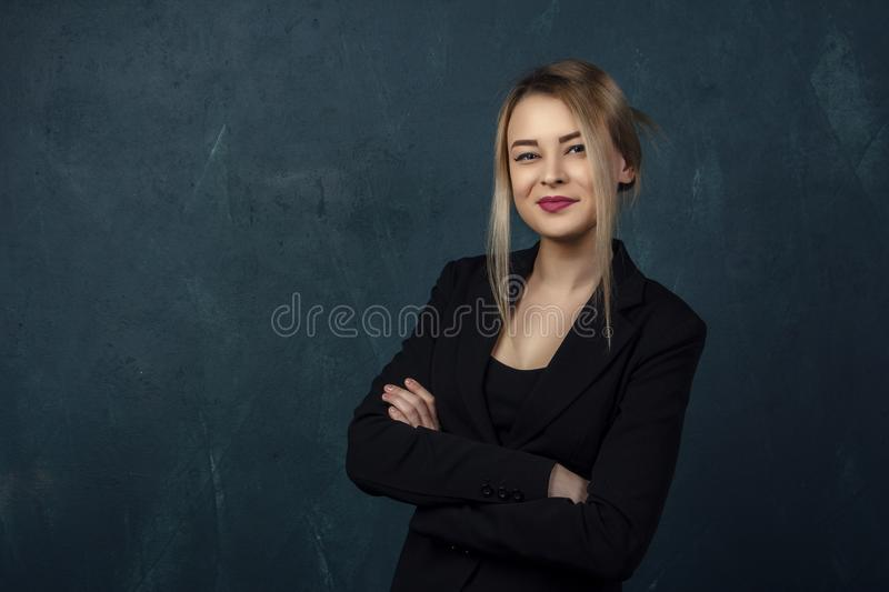 Close-up portrait with lots of details, beautiful smiling woman in black suit against a blue textural wall background with place f. Or text stock photography
