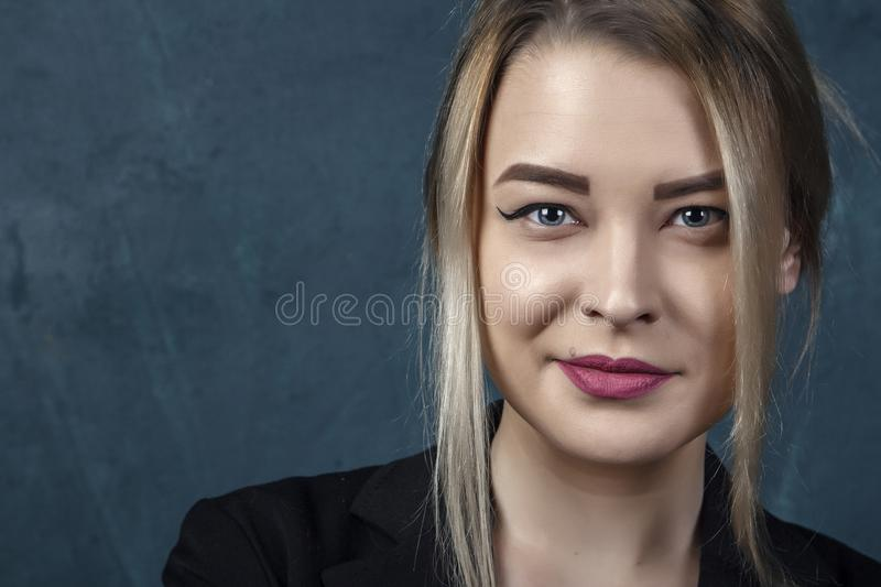 Close-up portrait with lots of details, beautiful smiling woman in black suit against a blue textural wall background with place f. Close-up portrait with lots royalty free stock photography