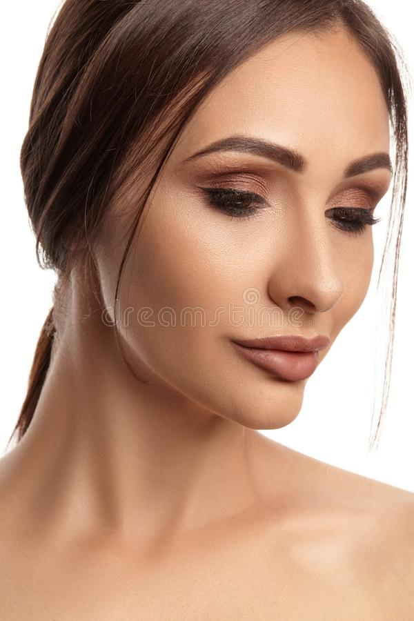 Close up portrait of a brunette nude model girl with professional evening make-up and plump lips, posing isolated on stock images