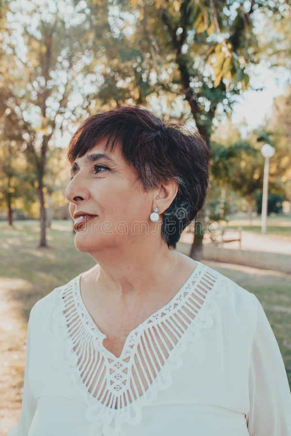 Close up portrait of lovely hispanic middle aged woman in the park stock photos
