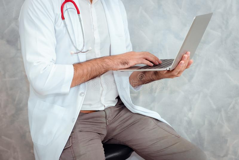 Close up portrait of male doctor using laptop to examining his p royalty free stock image