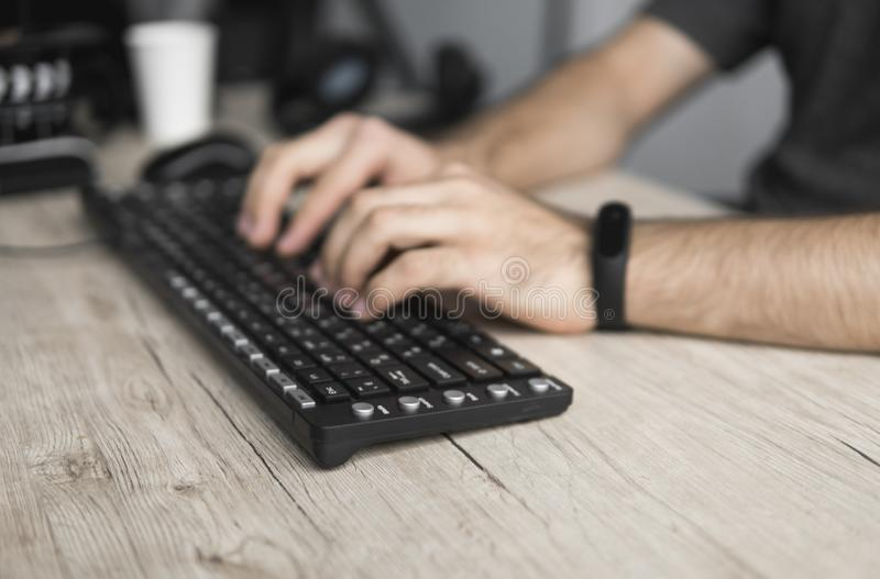 Close up portrait of male hands typing on computer keyboard. stock image
