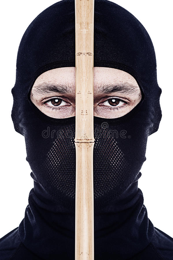 Close up portrait of male ninja. In black mask covered his face on white background stock images